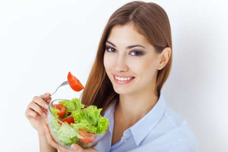 Closeup portrait of a happy young woman eating a fresh salad  photo