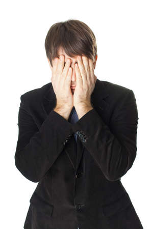 Young businessman covering his face with his hands isolated on white background photo