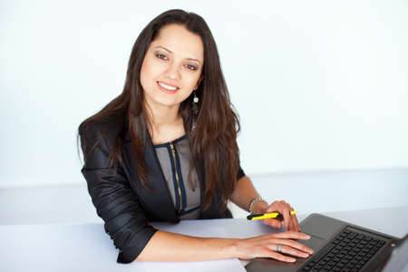 Portrait of beautiful young smiling brunette business woman working on a laptop in office Stock Photo - 22003782
