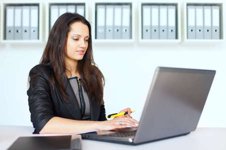 Portrait of beautiful young brunette business woman working on a laptop in office Stock Photo - 22003783