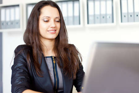 Portrait of beautiful young smiling brunette business woman working on a laptop in office Stock Photo - 22003785