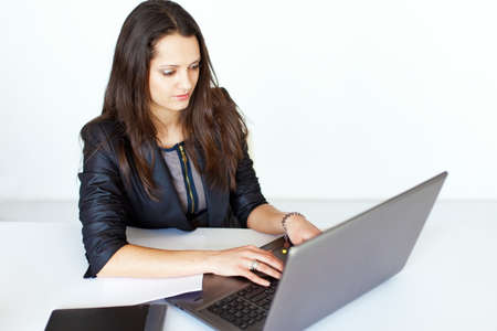 Portrait of beautiful young smiling brunette business woman working on a laptop in office Stock Photo - 22002787