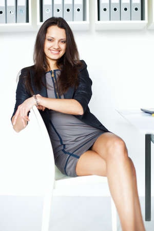 Portrait of young smiling brunette business woman sitting on a chair at the office photo
