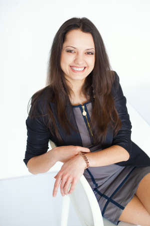 Portrait of young smiling brunette business woman sitting on a chair on white background photo