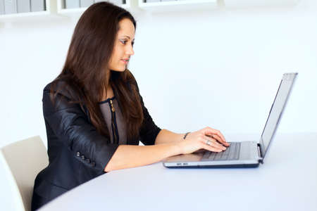 young women only: Portrait of beautiful young brunette business woman working on a laptop in office Stock Photo