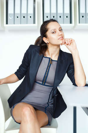 Portrait of young contemplative business woman sitting at the desk in office photo