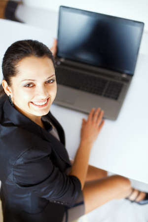 turn back: Top view portrait of beautiful young smiling brunette business woman working on a laptop in office,looking back Stock Photo