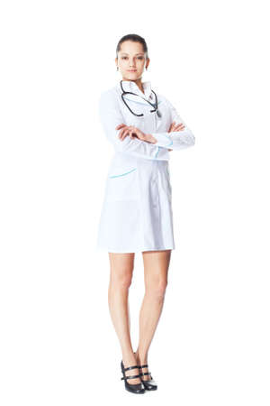 Full length portrait of young smiling woman doctor with arms crossed isolated on white background photo