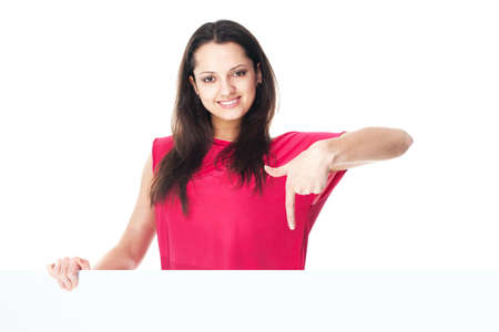 Portrait of pretty young smiling woman in red dress showing blank signboard isolated on white background photo