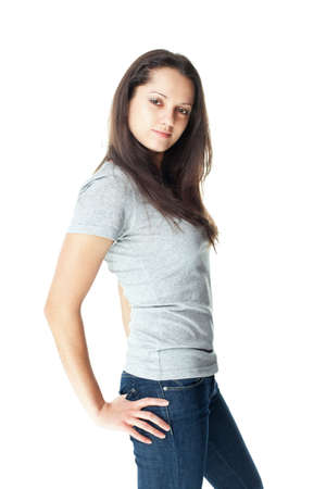 Portrait of pretty young brunette woman wearing blue jeans and gray t-shirt isolated on white background photo