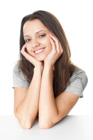 Portrait of pretty young brunette woman with elbows on the table and chin based on the hands isolated on white background photo