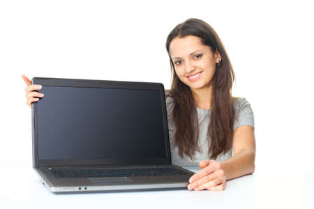 Portrait of pretty young brunette woman showing a laptop isolated on white background photo