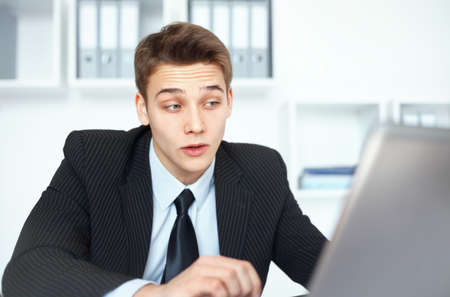 Young handsome businessman working on laptop in bright office photo
