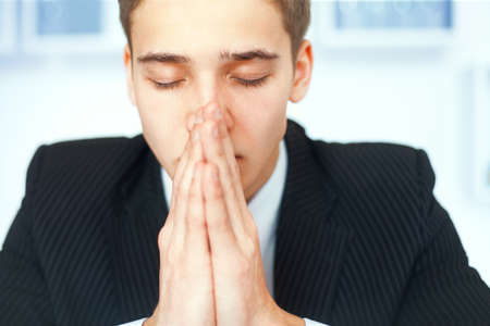 Closeup portrait of praying young businessman with eyes closed in office photo