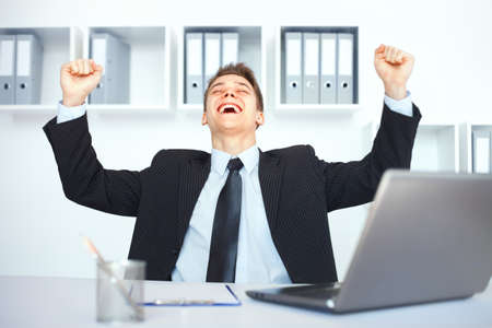 Giovane uomo d'affari che celebra il suo successo con le braccia alzate al suo posto di lavoro in ufficio brillante