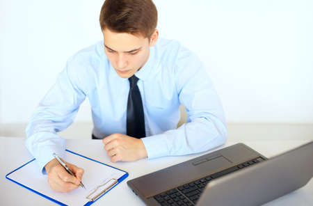 Young businessman writing on clipboard at his workplace in bright office photo