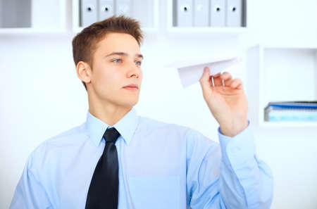 Portrait of young businessman launch a paper airplane at his workplace in bright office photo