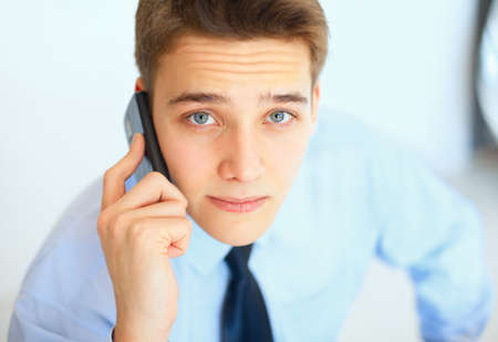 Portrait of young businessman talking on cell phone in office photo