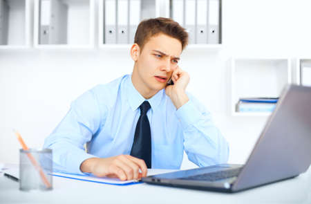 worried man: Portrait of young pensive businessman talking on cell phone in office