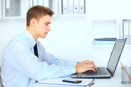 Side view young serious businessman working on laptop in bright office photo