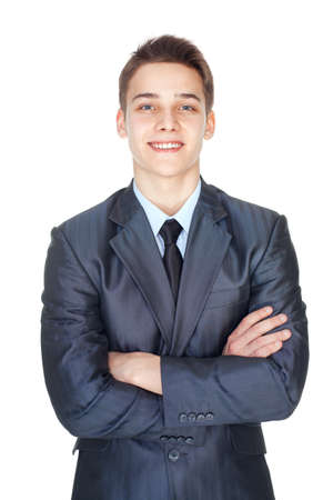 Portrait of handsome young smiling successful businessman standing with hands folded against isolated on white background photo