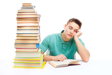Young tired student sitting at the desk with high books stack isolated on white background  photo