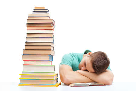 Sleeping student sitting at the desk with high books stack isolated on white background photo