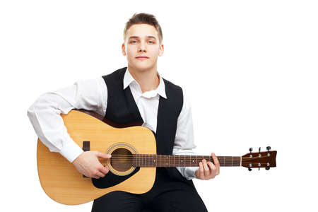 Young man playing on acoustic guitar sitting on a chair isolated on white background photo