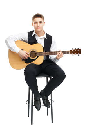 1 boy only: Young man playing on acoustic guitar sitting on a chair isolated on white background