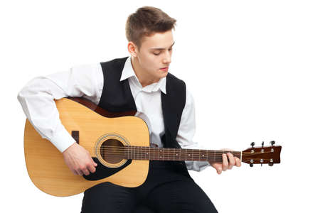 play popular: Young man playing on acoustic guitar sitting on a chair isolated on white background