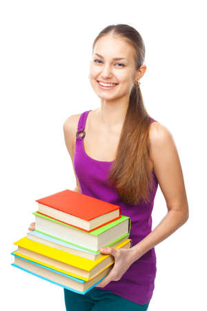 Portrait of a pretty young happy smiling student girl holding stack of books isolated on white background Stock Photo