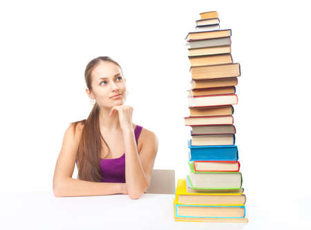 Portrait of pretty young smiling student girl sitting at the table looking at high stack of books isolated on white background photo