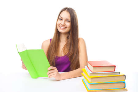 Portrait of pretty young happy smiling student girl reading a books at the table isolated on white background photo