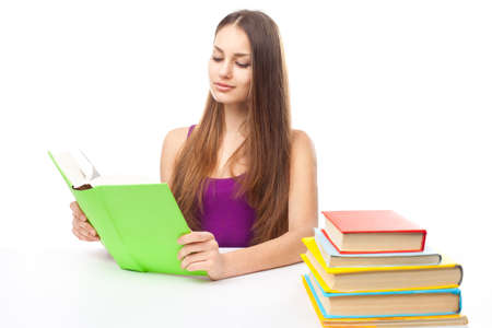 Portrait of pretty young smiling student girl reading a books at the table isolated on white background Stock Photo - 22003544