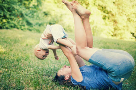 Mother and son having fun on the grass in a park  photo