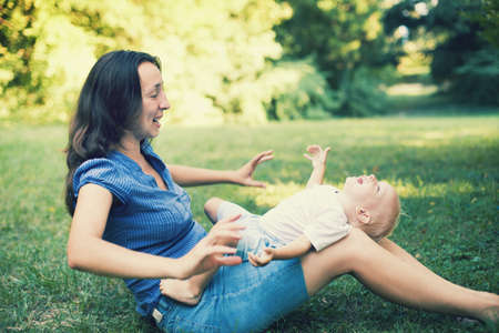 Mother and son having fun on the grass in a park Stock Photo - 22003608