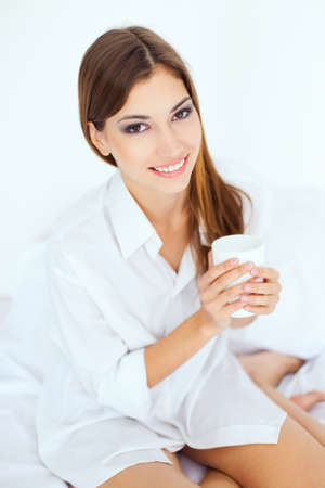 Beautiful smiling young woman in bed with a cup of coffee Stock Photo - 22003666