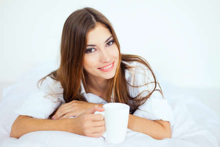 Beautiful smiling young woman in bed with a cup of coffee  Stock Photo - 22003667