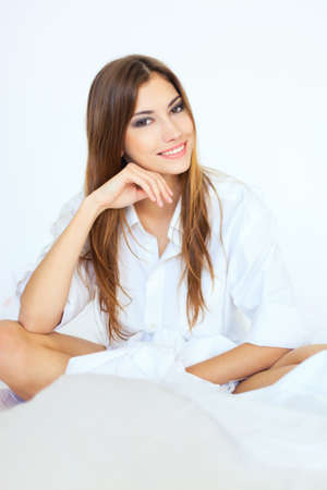Beautiful happy smiling young woman sitting on bed Stock Photo - 22003671