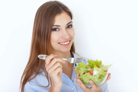 Closeup portrait of a happy young woman eating a fresh salad Stock Photo - 22003672