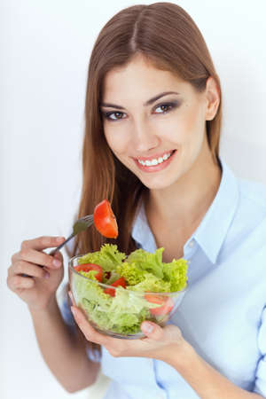 Closeup portrait of a happy young woman eating a fresh salad Stock Photo - 22003673