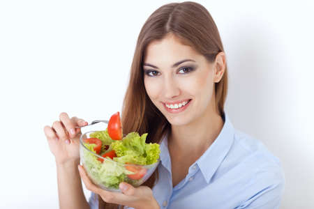 Closeup portrait of a happy young woman eating a fresh salad  Stock Photo - 22003674
