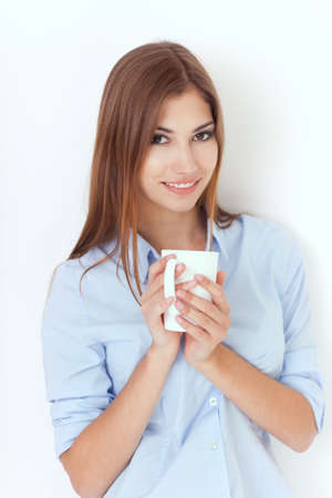 Portrait of a young woman with cup of tea or coffee  Stock Photo - 22003675