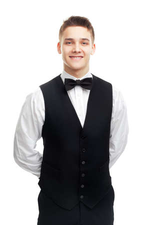 Portrait of young smiling waiter standing with hands behind his back isolated on white background