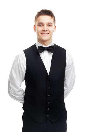 Ritratto di giovane cameriere sorridente in piedi con le mani dietro la schiena isolato su sfondo bianco