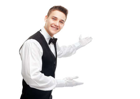 Portrait of young happy smiling waiter gesturing welcome isolated on white background Stock Photo