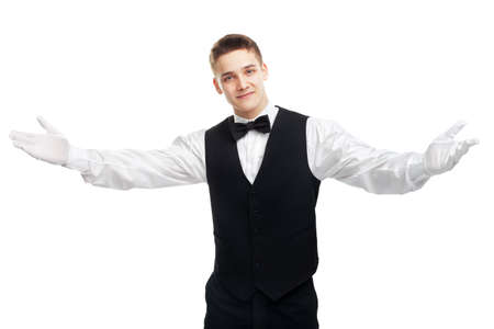 Portrait of young happy smiling waiter opens his arms in welcome isolated on white background photo
