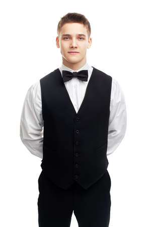 hands behind back: Portrait of young smiling waiter standing with hands behind his back isolated on white background