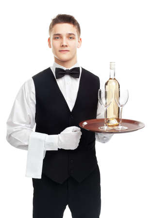 young waiter with bottle of white wine and stemware glass on tray isolated on white background photo