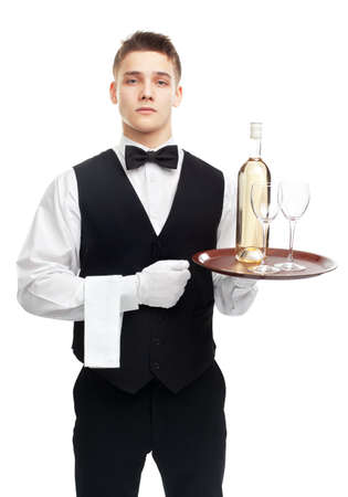 Portrait of young serious waiter with bottle of white wine and stemware glass on tray isolated on white background photo